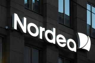 Illuminated Nordea sign on the wall during evening