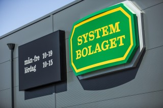 Systembolaget light box on a grey wall in Sweden