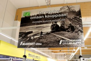 Printed black and grey banner in a grocery store in Finland