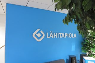 White LähiTapiola signage letters on a light blue wall